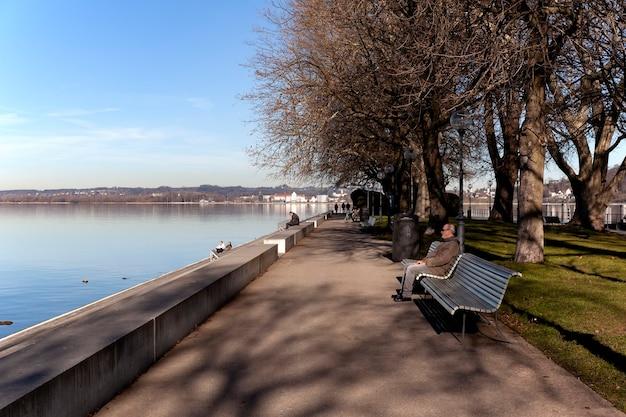 Begenz / austria - styczeń 2020: ludzie wypoczywają na ławkach i spacerują wzdłuż promenady jeziora bodeńskiego (bodensee) w bregencji.