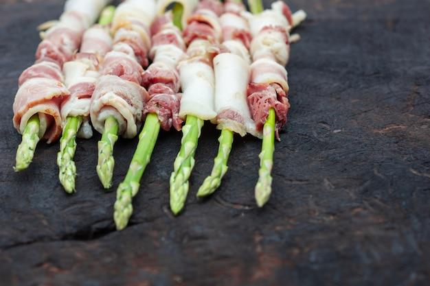 Bekon zawijający asparagus na drewnianym tle