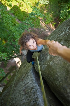 Belayer pomaga pięknym wspinaczkom, aby dotrzeć na szczyt