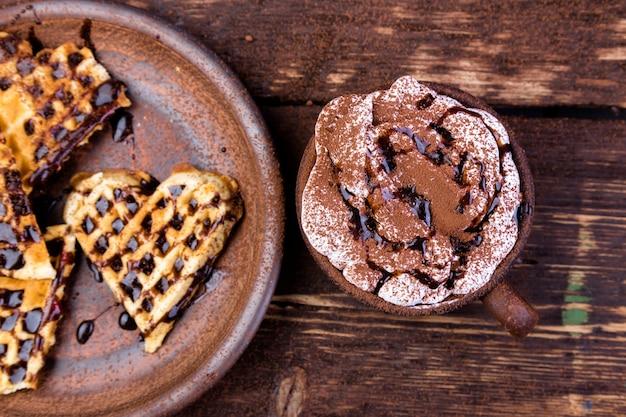 Belgijski gofr w kształcie serca na brązowym talerzu, z gorącą czekoladą z pianką