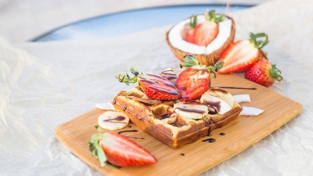 Belgijski gofr z sosem owocowo-czekoladowym jest pięknie podawany na drewnianej desce