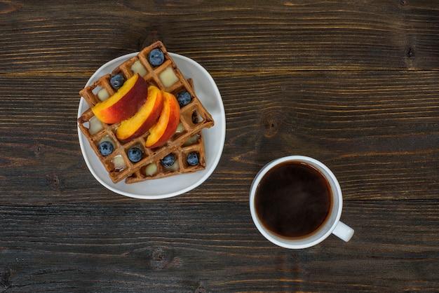 Belgijskie gofry czekoladowe z owocami i filiżanką kawy. pyszne śniadanie. widok z góry