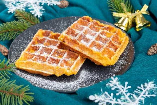 Belgijskie gofry na czarnym talerzu posypane cukrem pudrem. świąteczny i noworoczny nastrój. płatki śniegu, szyszki, gałęzie sosny na turkusowej tkaninie.