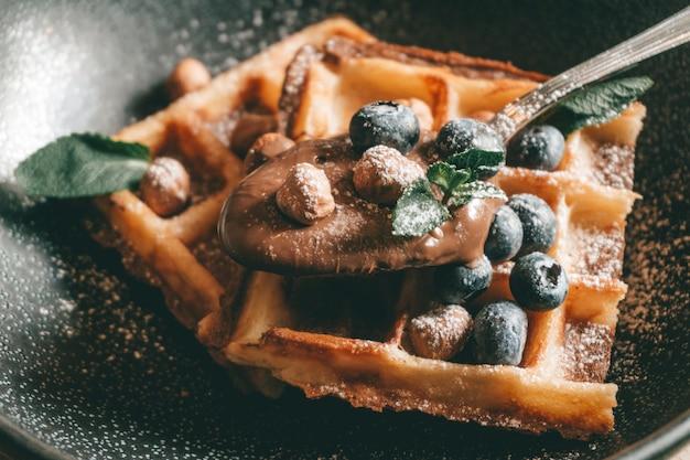 Belgijskie gofry z jagodami, lodami i czekoladą. ustawienie stołu śniadaniowego. poranny styl życia.