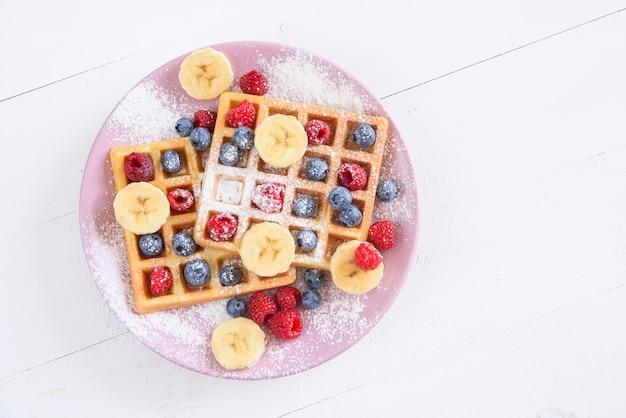 Belgijskie gofry z jagodami, malinami, bananami i cukrem w proszku. koncepcja smacznego i zdrowego jedzenia. widok z góry.