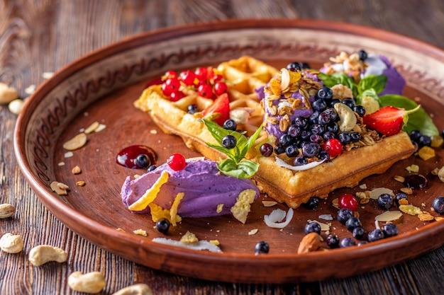 Belgijskie gofry z kremem jagodowym, muesli i świeżych jagód, smaczne śniadanie, orientacja pozioma, zbliżenie