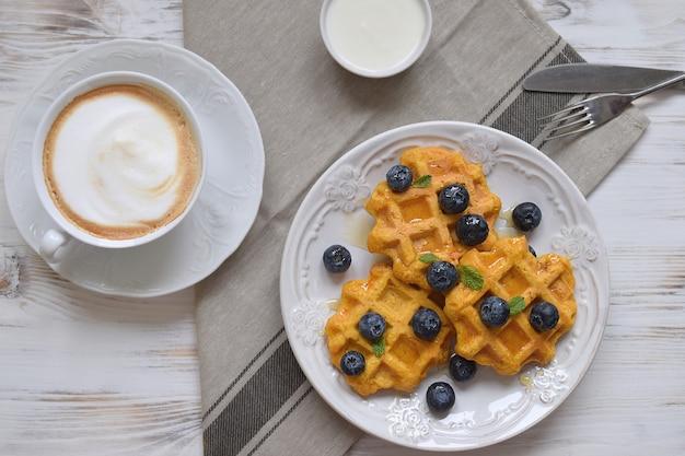 Belgijskie gofry zdrowe śniadanie jagoda miód mięta kwaśna śmietana kawa cappuccino białe drewniane widok z góry mieszkanie leżał