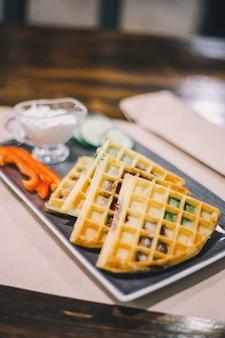 Belgijskie kanapki z goframi z pieczonymi pomidorami, ogórkiem, pieprzem i sosem podawane na prostokątnej płycie w kawiarni