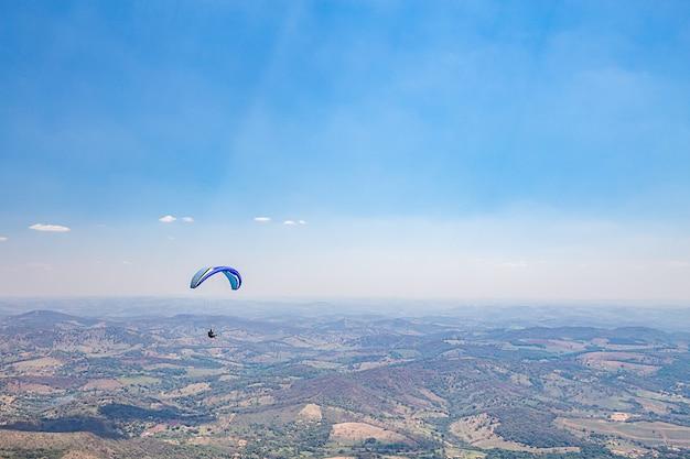 Belo horizonte, minas gerais, brazylia. paralotnia lecąca ze szczytu góry świata