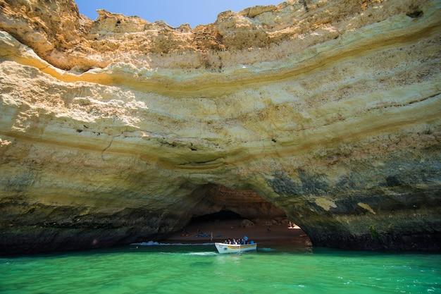 Benagil cave boat tour w algar de benagil, jaskini wymienionej w 10 najlepszych jaskiniach na świecie. wybrzeże algarve w pobliżu lagoa, portugalia. turyści odwiedzają popularny punkt orientacyjny