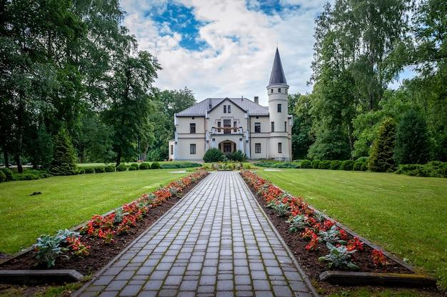 Bene, łotwa - 3 lipca 2020 r .: droga prowadzi przez park do starego dworu. bene manor.
