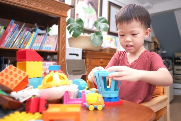 Berbeć bawić się zabawkami, śliczny mały azjatycki berbeć chłopiec dzieciak ma zabawę bawić się z kolorowymi plastikowymi blokami salowymi w domu