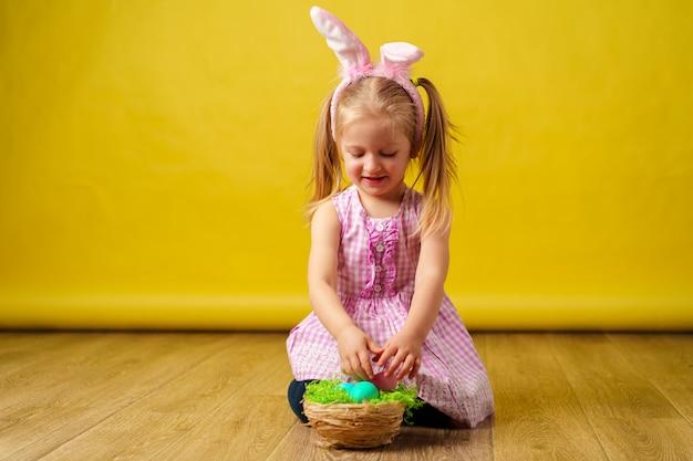 Berbeć blondynki szczęśliwa dziewczyna z królików ucho i koszem jajka na wielkanoc