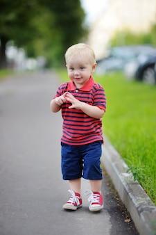 Berbeć chłopiec bawić się w mieście przy wiosną lub letnim dniem