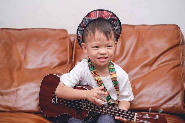 Berbeć chłopiec dziecko jest ubranym kapeluszowego chwyt & bawić się hawajską gitarę lub ukulele w żywym pokoju