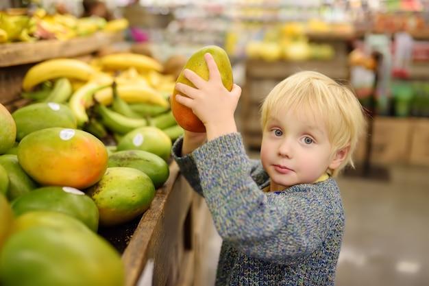 Berbeć chłopiec w sklepie spożywczym lub supermarkecie wybiera świeżego organicznie mango