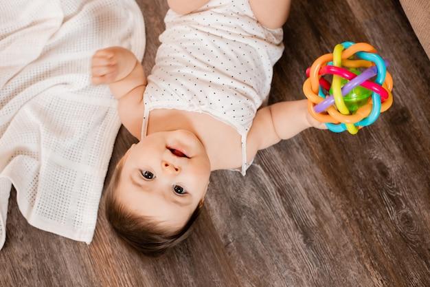 Berbeć dziewczyna kłama na drewnianej podłoga bawić się z rozwijającą się zabawką