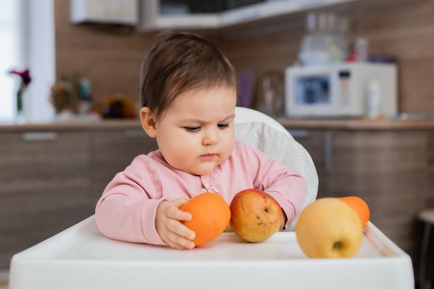 Berbeć dziewczyna siedzi na dziecięcym krześle w kuchni bawić się z owocami