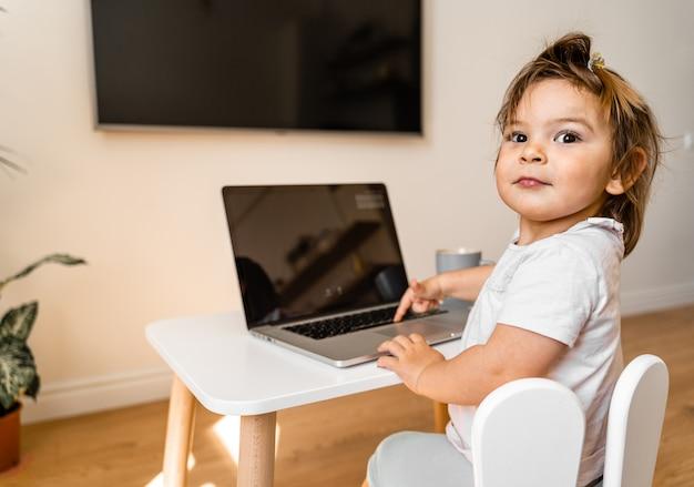 Berbeć dziewczyna używa laptop na jej stole. widok z góry. edukacja online