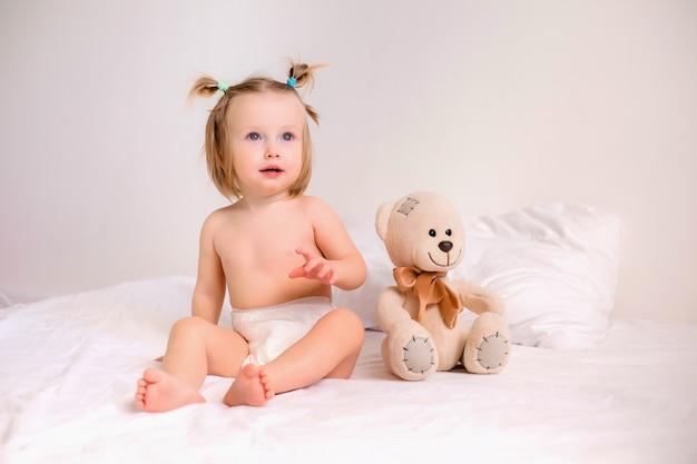 Berbeć dziewczyna w pieluszkach siedzi z zabawkowym niedźwiedziem na łóżku w domu