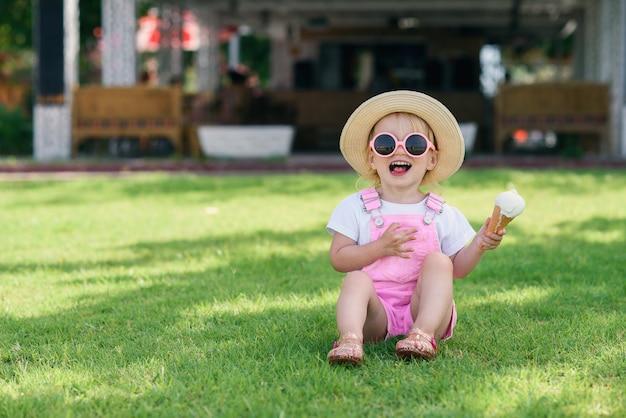 Berbeć dziewczyna w różowym letnim kombinezonie, kapeluszu i różowych okularach przeciwsłonecznych siedzi na zielonej trawie z lodami w ręku i uśmiecha się.