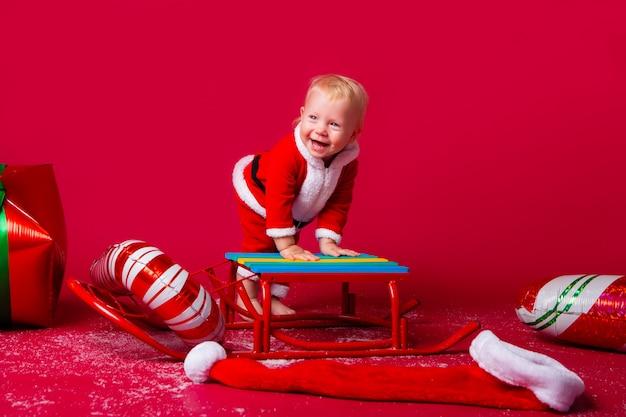 Berbeć dziewczyna w santa kostiumu na saniu z nowy rok prezentami na czerwonej ścianie