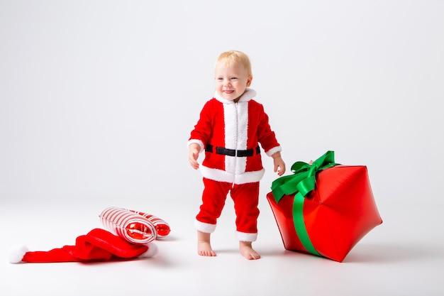 Berbeć dziewczyna w santa kostiumu z nowy rok prezentami na białej ścianie