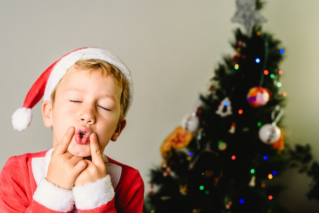 Berbeć z święty mikołaj kostiumem robi twarzom obok choinki, boże narodzenie wakacje pojęcie.