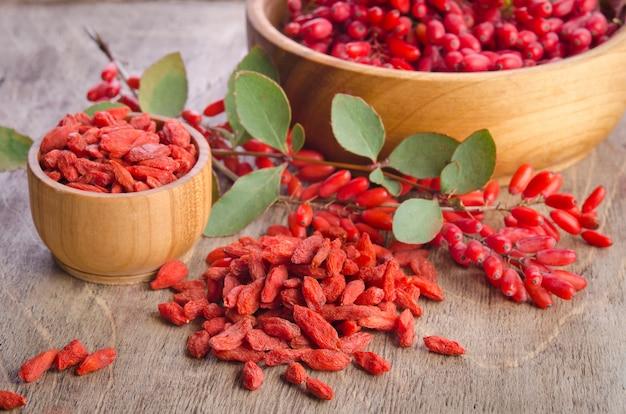 Berberys i suche jagody goji w miskach na drewnianych