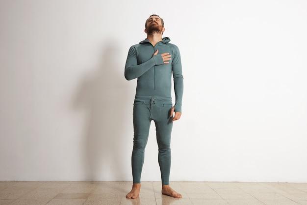 Berded dopasowany mężczyzna w uschniętym ubraniu termicznym trzyma rękę na sercu i patrzy w górę inspirująco, na białym tle