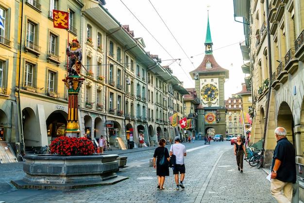 Berno, szwajcaria - 23 sierpnia 2018: ludzie na alejce handlowej z astronomiczną wieżą zegarową zytglogge w bernie w szwajcarii