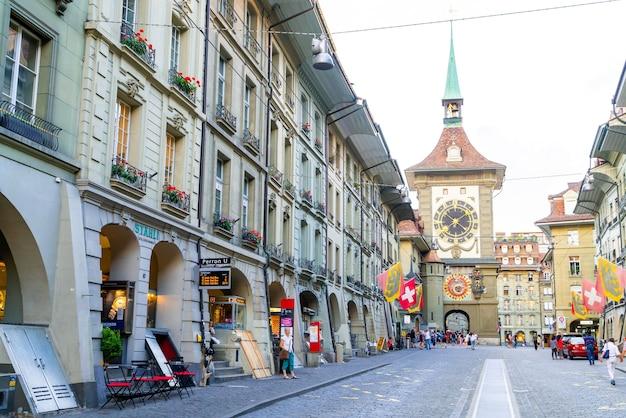 Berno, szwajcaria - ludzie na ulicy handlowej z wieżą zegara astronomicznego zytglogge w bernie w szwajcarii