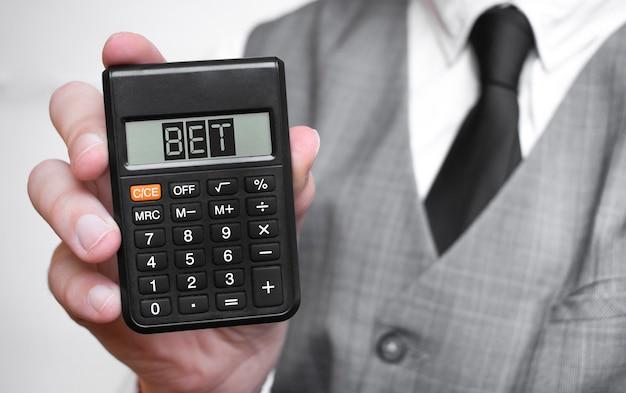 Bet słowo tekst napis na kalkulatorze w męskiej dłoni biznesmena w białej koszuli i niebieskim krawacie