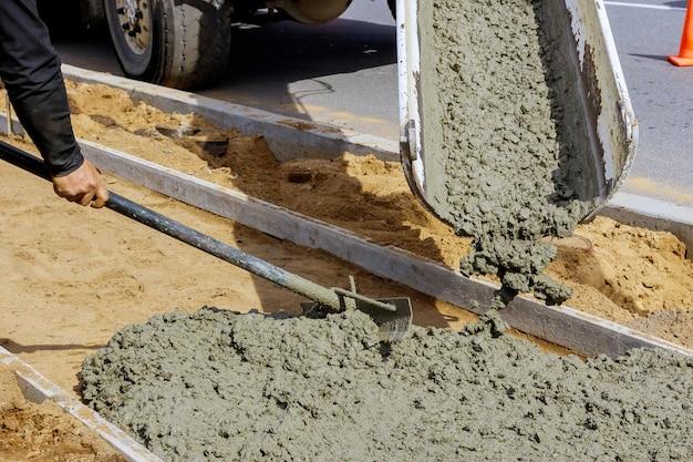 Beton wylewa się z ciężarówki na beton z chodnikiem