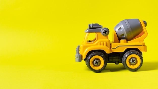 Betoniarka maszyna budowlana na żółtym tle z miejscem na tekst