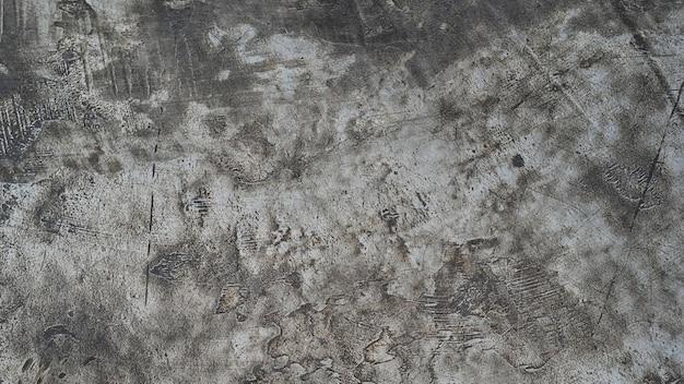 Betonowa nieociosana podłoga z ciemnym tekstury tłem.
