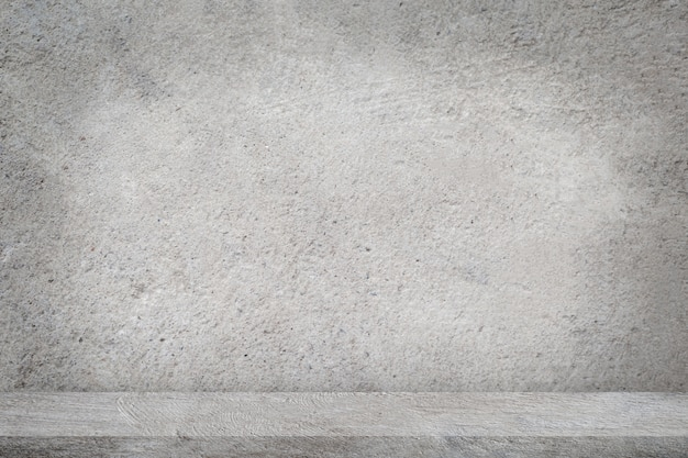 Betonowa podłoga z pustym szarym betonowej ściany tłem.