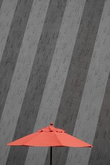 Betonowa ściana budynku z czerwonym parasolem