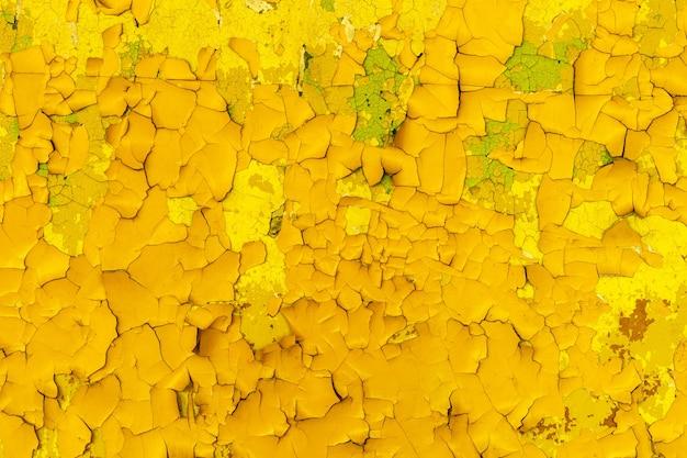 Betonowa ściana z żółtą farbą w pęknięciach. tło dla projektu. grunge tekstur. zdjęcie wysokiej jakości