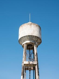 Betonowa wieża ciśnień z metalową drabiną.
