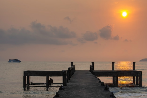 Betonowe filary pomostowe i odbicie słońca w morzu.