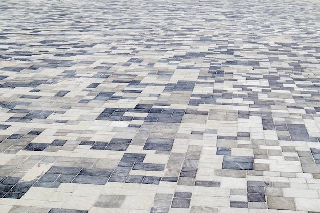 Betonowe lub brukowane nowo ułożone szare płyty chodnikowe lub kamienie na podłogi lub chodniki. betonowe płyty chodnikowe na podwórku lub nawierzchni drogowej. ścieżka ogrodowa murowana na dziedzińcu na podmurówce z piasku.