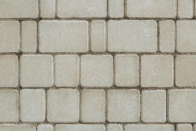 Betonowe lub brukowane szare kwadratowe płyty chodnikowe lub kamienie na podłogę, ścianę lub ścieżkę