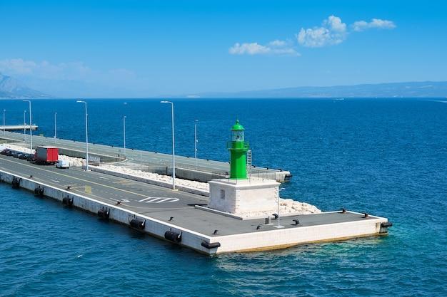 Betonowe nowoczesne molo z kilkoma samochodami i zieloną latarnią, obszar portu w splicie nad morzem adriatyckim.