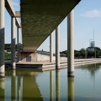 Betonowy most nad stawem pod niebieskim niebem