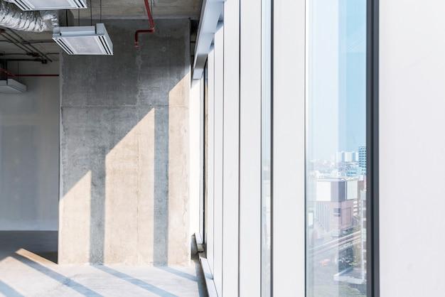 Betonowy słup oświetlony światłem słonecznym podczas remontu wnętrza przy pracach w systemie sufitów otwartych. pusta przestrzeń pod inwestycję deweloperską.