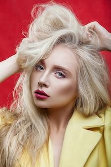 Beuty portier dziewczyna z siwymi włosami na czerwonym tle. piękna fryzura i makijaż.