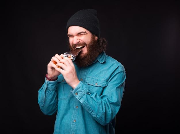 Bez diety. hipster brodaty mężczyzna w niebieskiej koszuli jedzenie ciemnej czekolady