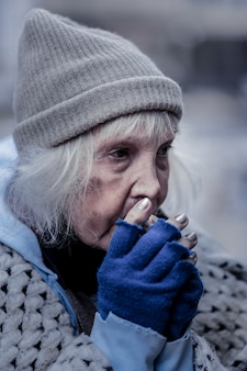 Bez domu. smutna biedna kobieta przebywa zimą na zewnątrz, nie mając domu