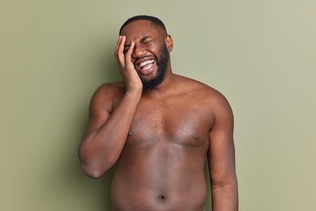 Bez koszuli, brodaty mężczyzna sprawia, że twarz dłoniowa śmieje się radośnie z czegoś pozytywnego, ma białe, idealne zęby stoi w studiu pod ciemnozieloną ścianą